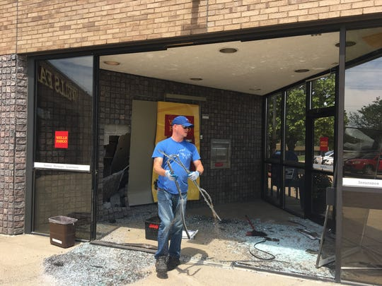 Jason Theisen with East Side Glass Company works to clear the damage Thursday, June 21, from the Wells Fargo bank at 33rd Avenue and Third Street North.