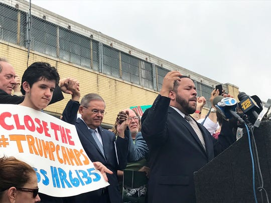 U.S. Sen. Bob Menendez, left center, holds hands with faith leaders as Newark Pastor Pablo Pizarro leads protesters in a prayer Friday morning outside the Elizabeth Detention Center, Friday, June 22, 2018.
