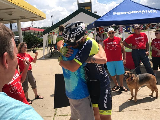 Joe Lawhorn embraces one of the more than 50 extended family members and friends who waited for his arrival at the East Main Street timing station early Friday afternoon.