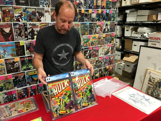"Chris Rupp, owner of Rupp's Comics, is seen here holding two copies of ""Incredible Hulk #18,"" the comic book that features the first appearance of Wolverine."