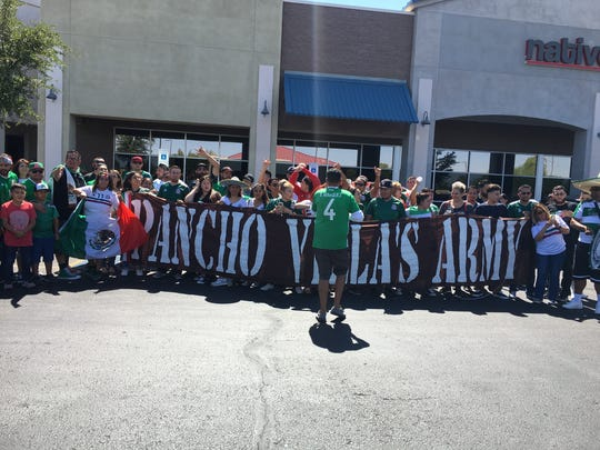 Adrian Zarate organizes the members of the Pancho Villa's Army Phoenix Battalion into a group to take a picture after Mexico's 2-1 win over South Korea in the World Cup