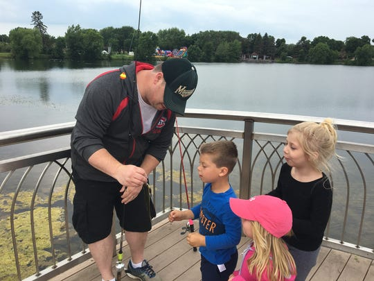 Carey Groethe shows a just-reeled fish to his kids