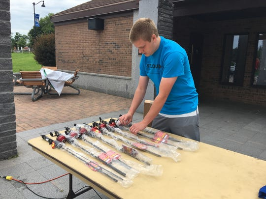 """Jacob Zimmer sets up new fishing rods and other prizes before the """"Bring a Kid Fishing Day"""" on Sunday, June 24."""