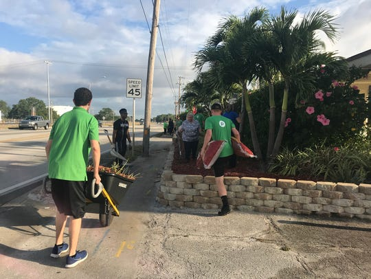 Publix employees trim bushes and clean up the grounds