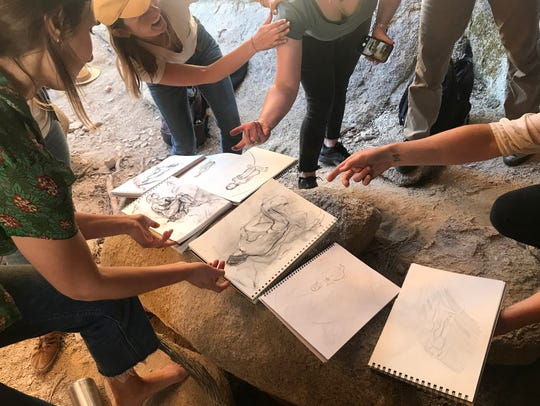 Participants show their sketches in cave in Joshua