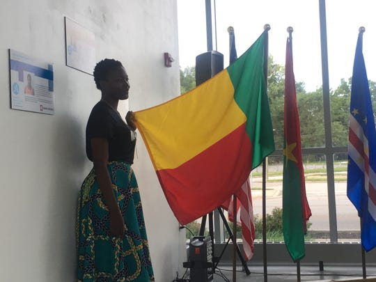 : Monbolade Urchelle Pamela Akologan stands with the flag of her country, Benin, at the Mandela Washington Fellowship networking event at IUPUI.
