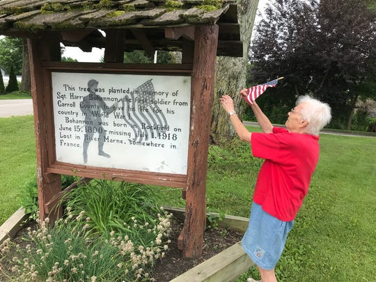 Marjorie Been, a lifelong Rockfield resident, replaces a U.S. flag at a monument marking a tree planted nearly a century ago to honor Sgt. Harry Bohannon, a Rockfield native who died July 1, 1918, during a mission on the Marne River in France during World War I.