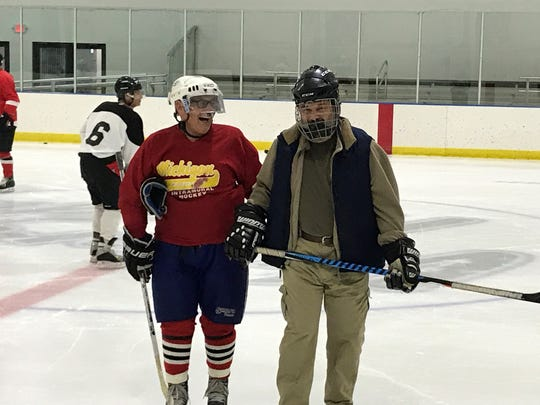Father Dimitrie Vincent (right) skates slowly, but