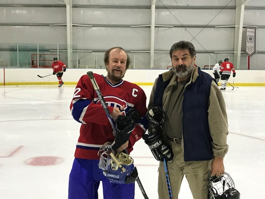 Gary Swain (left) is commissioner of Plymouth Puckmasters. He shares an on-ice reunion with Father Dimitrie Vincent.