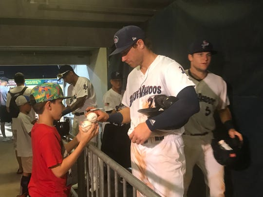 Blue Wahoos third baseman Taylor Sparks signs autographs for a young fan following the team's 10-5 win Thursday night against M-Braves.