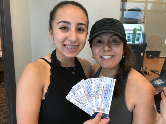 Khalid fan Karyme Aviña, 15, and mom Leticia Aviña hold up their concert tickets. They had to split up their seats in two sections to get six.