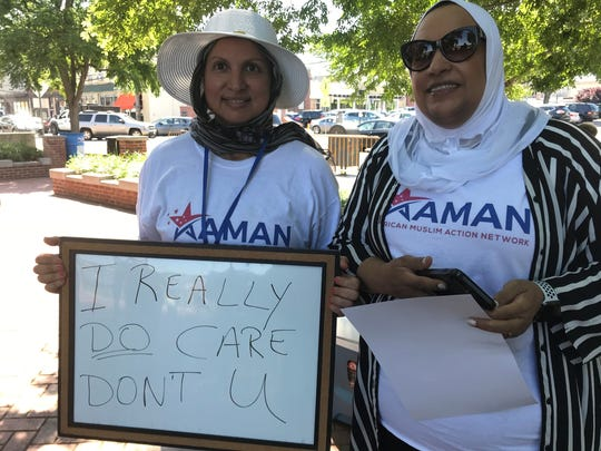 """Nagwa Awad and Nour Elbarrad, board members of the American Muslim Action Network in Monmouth County, join the protest at Riverside Garden Park in Red Bank. Awad wrote on a whiteboard, """"I really do care, don't u?"""" in response to a green jacket worn by First Lady Melanie Trump during a visit to the border that read """"I really don't care, do u?"""""""