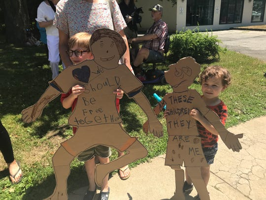 Children holding protest signs at Saturday's Families