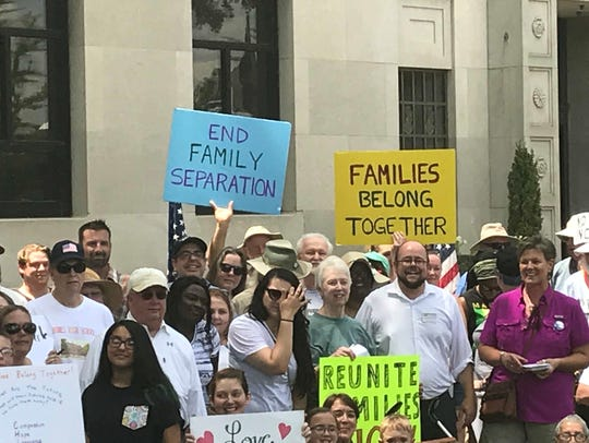 Protesters hold signs with messages against family