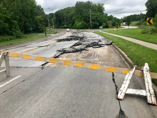 Pavement gnarled by floodwaters near the intersection