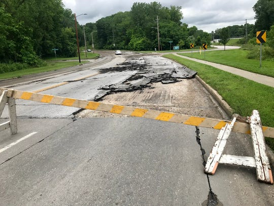 Pavement gnarled by floodwaters near the intersection of Hickman and Prospect roads on Des Moines north side following heaving rains on Saturday, June 30, 2018.
