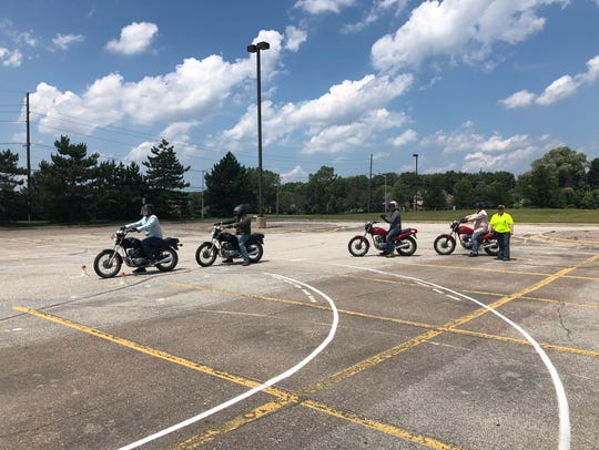 New riders participate in a riding exercise in a parking