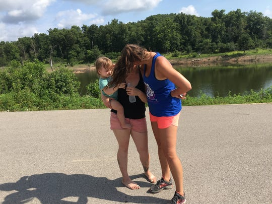 Pamela Crim, right, comforts a mother and toddler Monday