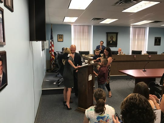 Robbie Vargo hugs Cedar Grove Councilwoman Kerry Peterson after she swears him in as deputy mayor, as the Vargo's wife Chelsea, and children Preston, Jackson and Aiden look on.