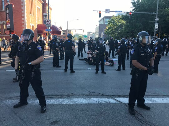 Officers in riot gear surround seated demonstrators Saturday at a Black Lives Matter protest.