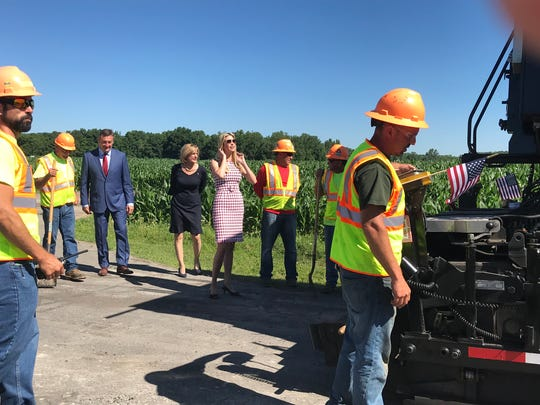 Ivanka Trump, Congresswoman Cluaudia Tenny and business owner Frank Suits watch a machine pave a part of road