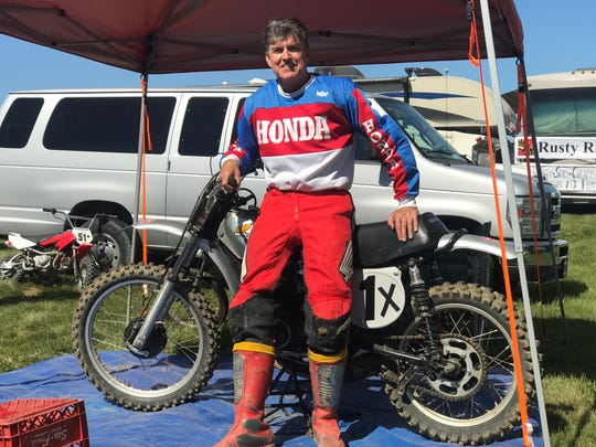 Vintage supercross racer Steve Ellis poses with his bike after winning the 60+ age group race at the AMA Vintage Motorcycle Days at Mid-Ohio on Saturday