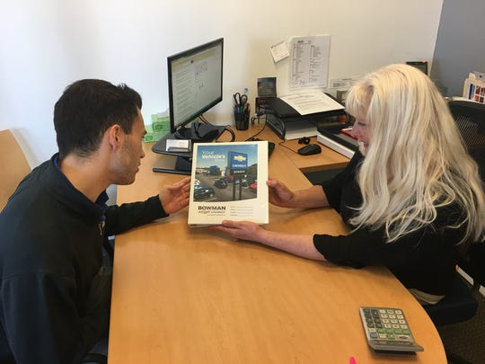 Peggy Trapp, Bowman Chevrolet business manager and Connor Bright, assistant business manager, prepare a vehicle storybook for a customer.