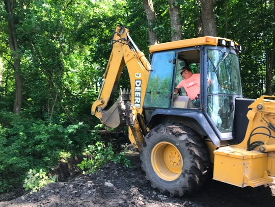 Mike Patty, grandfather of Libby German, uses a backhoe