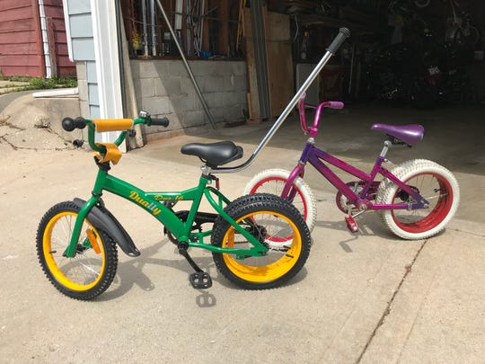 The first dually bicycles stand in front of the garage of their inventor, Jeffrey Gaudynski. Both feature the dual rear tires that give the bicycles more stability. The bike in the back was the first working model. The green bike in front is from the first batch of newly manufactured dually bicycles.
