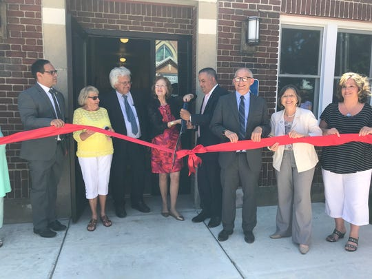 Binghamton Mayor Richard David, fourth from the right, and Assemblywoman Donna Lupardo, second from right, at the ribbon-cutting of the completed E.J. Apartments.