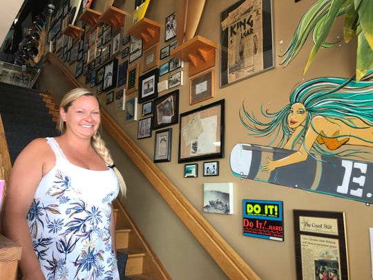 Darby Tarrant in front of the wall display of Belmar