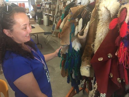 Pageant volunteer Cherlyn Thornton shares costumes that will be displayed in the performance.