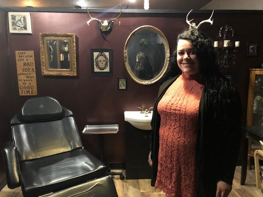 Courtney Deppe stands in her piercing and tattooing
