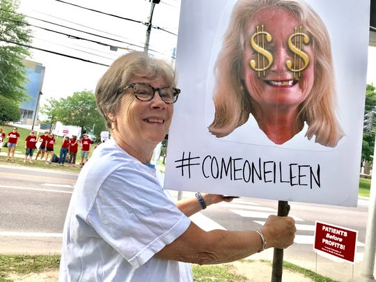 Marley Skiff, a retired nurse, holds a sign at the picket line on Colchester Avenue on Friday, July 13, 2018. She wore an early 21st-century nurses union t-shirt as she supported University of Vermont Medical Center nurses on strike. She holds a sign referring to hospital president Eileen Whalen.