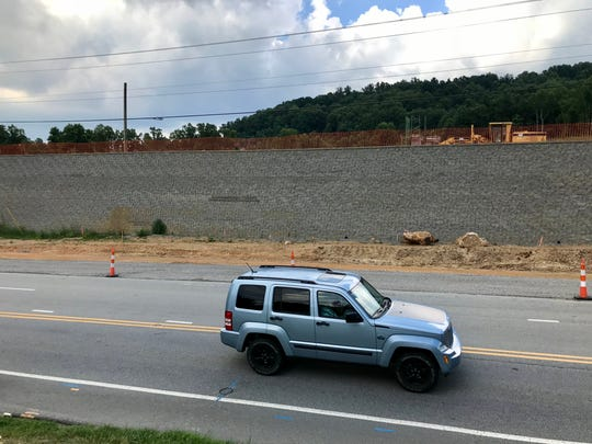 The developer of the Hawthorne on Mills Gap apartments says the appearance of this large retaining wall will be softened by a berm and landscaping running its entire length. Initially, it was to be a terraced wall, but the widening of Mills Gap Road took that option out of play.