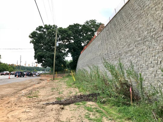 The widening of Mills Gap Road at the intersection of Sweeten Creek Road will necessitate removing a stand of large oaks at the end of the wall, the DOT said.