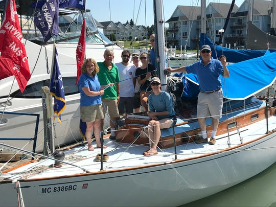 The crew of Albacore poses for a photo after working on their sailboat for the start of the Port Huron to Mackinac Island Sailboat Race.