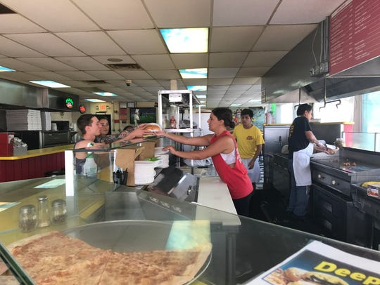 Steaks Unlimited's Sienna Faruolo serving a cheesesteak