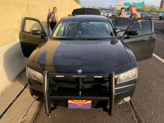 Officials said Matthew Allen Disbro, pictured in the background leaning against the wall along the freeway, equipped his car with emergency-style lights, sirens and a police scanner.