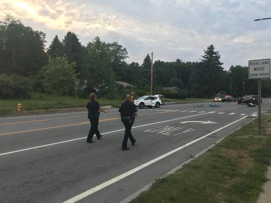 Technicians place evidence markers in the road following a collision on Route 250 on July 13, 2018,