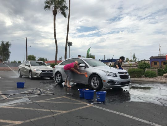 Two people wash a car during a fundraiser for Monique