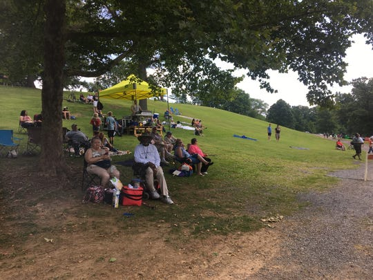 People watch a musical act at the Waynesboro Extravaganza on Saturday afternoon. Some are staking out their spots for the fireworks later.