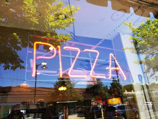 A neon sign at Buona Pizza advertises the house specialty