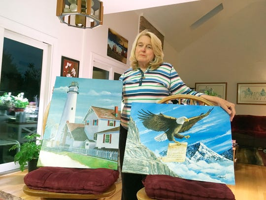 Former Department of Correction counselor Patricia May with paintings by Delaware prison inmates that decorate her home. May was taken hostage during the prison takeover in 2017.