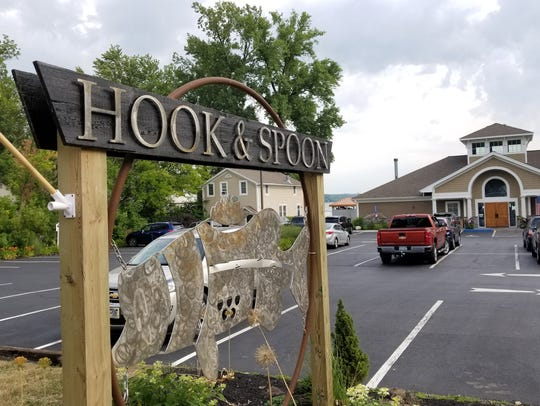 A fabricated fish sign greets guests at Hook & Spoon