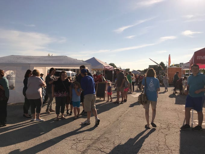 People linger at vendors' tents while listening to