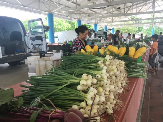 Vendor stalls at Fondy Farmers Market are in an open-air