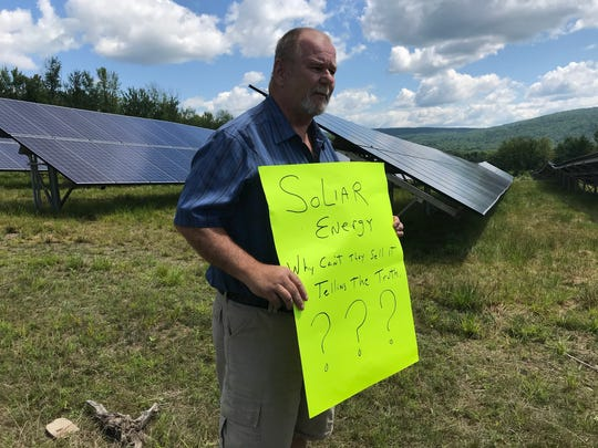 Victor Furman, a natural gas drilling advocate from Chenango Forks holds up a sign in front of Broome County solar panels.