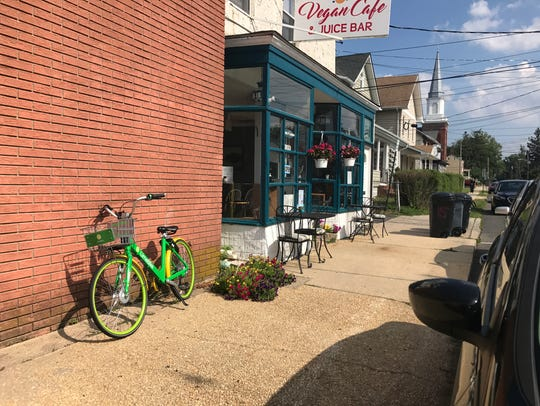 A LimeBike parked in front of a cafe on Main Street