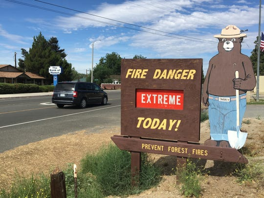 A sign outside an Anza fire station warns of the wildfire threat. Fire officials say area mountains are covered in dry vegetation that make the area prone to wildfires.